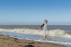 Ώριμη γυναίκα που περπατά στη θάλασσα Στοκ Εικόνα