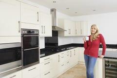 Ώριμη γυναίκα που στέκεται στη νέα εγκατεστημένη πολυτέλεια κουζίνα Στοκ Εικόνα