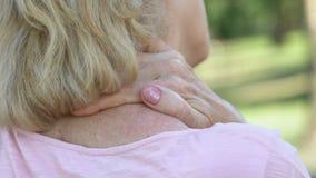 Ώριμη γυναίκα που τρίβει το ναρκωμένους λαιμό και τους ώμους, συνέπειες τραυματισμών σπονδυλικών στηλών φιλμ μικρού μήκους
