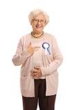 Ώριμη γυναίκα που φορά μια κορδέλλα και μια υπόδειξη βραβείων Στοκ φωτογραφίες με δικαίωμα ελεύθερης χρήσης