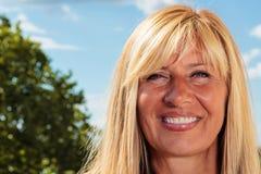Ώριμη γυναίκα που χαμογελά μια ηλιόλουστη ημέρα Στοκ Εικόνες
