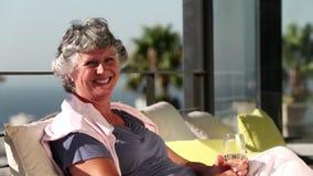 Ώριμη γυναίκα που χαμογελά στη κάμερα στο μπαλκόνι απόθεμα βίντεο