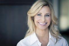 Ώριμη γυναίκα που χαμογελά στη κάμερα Στοκ Φωτογραφίες