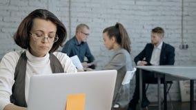 Ώριμη γυναίκα που χρησιμοποιεί το προσωπικό Η/Υ και την εργασία της στην αρχή απόθεμα βίντεο