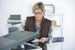 Ώριμη γυναίκα που χρησιμοποιεί το φωτοτυπικό μηχάνημα στο δημιουργικό γραφείο στοκ φωτογραφία