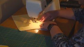 Ώριμη γυναίκα που χρησιμοποιεί skillfully μια ράβοντας μηχανή για να ράψει τους φραγμούς παπλωμάτων απόθεμα βίντεο