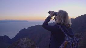 Ώριμη γυναίκα στις περιπέτειες πεζοπορίας σε μια κορυφή βουνών που εξετάζει τον ορίζοντα μέσω των διοπτρών φιλμ μικρού μήκους