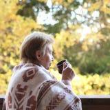 Ώριμη γυναίκα στο μάλλινο καρό που πίνει το καυτό ποτό στο terrac στοκ φωτογραφία με δικαίωμα ελεύθερης χρήσης