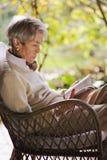 Ώριμη γυναικεία ανάγνωση και χαλάρωση υπαίθρια Στοκ Φωτογραφίες