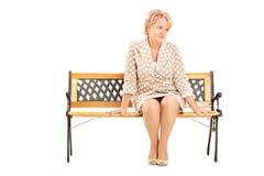 Ώριμη γυναικεία συνεδρίαση σε έναν πάγκο που απομονώνεται στο άσπρο υπόβαθρο Στοκ Φωτογραφία