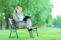Ώριμη γυναικεία χαλάρωση με ένα βιβλίο στο πάρκο Στοκ εικόνες με δικαίωμα ελεύθερης χρήσης