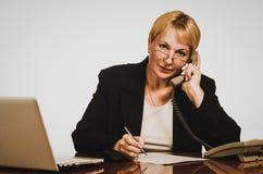 Ώριμη επιχειρηματίας που καλεί το τηλέφωνο στον εργασιακό χώρο της Στοκ Εικόνες