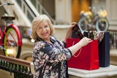 Ώριμη ευτυχής γυναίκα με τις τσάντες αγορών στοκ εικόνες