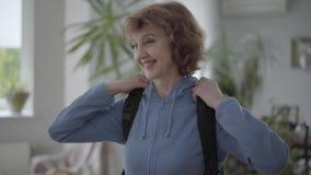 Ώριμη ευτυχής γυναίκα πορτρέτου στο μπλε hoody μαύρο άνετο σακίδιο πλάτης καθορισμού σε την πίσω απόθεμα βίντεο