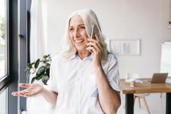 Ώριμη ευτυχής γυναίκα στο εσωτερικό στην αρχή Στοκ Φωτογραφία