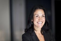 Ώριμη ισπανική επιχειρηματίας που χαμογελά και που κοιτάζει μακριά ο βραχίονας απαρίθμησε τη βασική όψη της Στοκ φωτογραφία με δικαίωμα ελεύθερης χρήσης