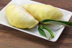 Ώριμη κίτρινη σάρκα Durian στο άσπρο πιάτο, ξύλινο υπόβαθρο Στοκ Εικόνες