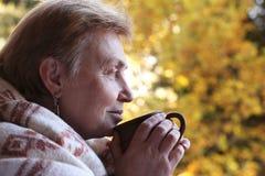Ώριμη κοντή μισθωμένη γυναίκα με το φλυτζάνι του τσαγιού και του μάλλινου καρό στοκ εικόνες