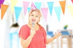 Ώριμη κυρία με το τραγούδι καπέλων κομμάτων στο μικρόφωνο στο κόμμα Στοκ Εικόνες