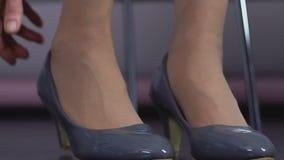 Ώριμη κυρία που προσπαθεί στο ζευγάρι των ολοκαίνουργιων λαμπρών παπουτσιών που κάθονται στο κατάστημα, γυναικεία φύση απόθεμα βίντεο