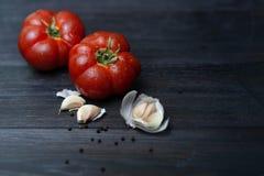 Ώριμη κόκκινη ντομάτα με τα καρυκεύματα στο σκοτεινό υπόβαθρο στοκ εικόνες