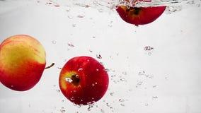 Ώριμη κόκκινη πτώση μήλων στο νερό με τις φυσαλίδες Βίντεο σε σε αργή κίνηση φιλμ μικρού μήκους
