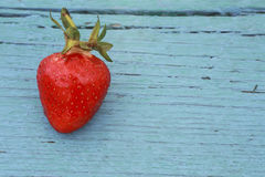 ώριμη κόκκινη φράουλα μούρων σε έναν μπλε πίνακα παλαιό Στοκ Φωτογραφίες
