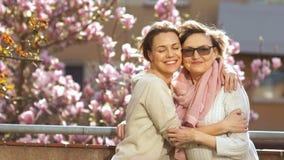 Ώριμη μητέρα και ενήλικο αγκάλιασμα κορών που στέκονται σε ένα μπαλκόνι σε ένα υπόβαθρο του ανθίζοντας δέντρου του magnolia Φωτει απόθεμα βίντεο