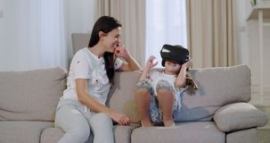 Ώριμη μητέρα με τη μικρή κόρη της που εξερευνά τον εικονικό κόσμο που χ απόθεμα βίντεο
