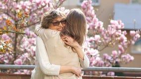 Ώριμη μητέρα που αγκαλιάζει την ενήλικη κόρη της Χρόνια πολλά Άνθιση άνοιξη του magnolia, μόνο γυναίκες απόθεμα βίντεο