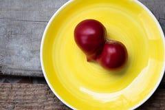 Ώριμη ντομάτα στη μορφή καρδιών στο κίτρινο πιάτο Στοκ Φωτογραφία