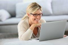 Ώριμη ξανθή γυναίκα που χρησιμοποιεί το lap-top στο σπίτι στοκ εικόνα με δικαίωμα ελεύθερης χρήσης