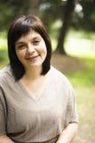 Ώριμη παχιά γυναίκα brunette στον πράσινο κήπο, χαμόγελο, φιλικό wel στοκ φωτογραφία με δικαίωμα ελεύθερης χρήσης