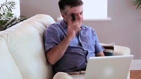 Ώριμη συνεδρίαση ατόμων στον καναπέ χρησιμοποιώντας το lap-top και απαντώντας στο τηλέφωνό του απόθεμα βίντεο