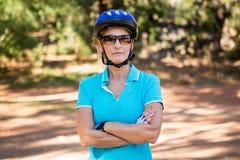 Ώριμη τοποθέτηση γυναικών αναβατών ποδηλάτων με τα όπλα που διασχίζονται Στοκ εικόνες με δικαίωμα ελεύθερης χρήσης