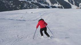 Ώριμη χάραξη σκιέρ γυναικών κάτω από την κλίση στο χιονοδρομικό κέντρο βουνών στο χειμώνα απόθεμα βίντεο