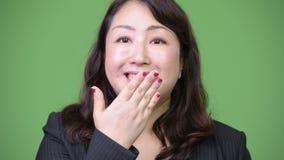 Ώριμη όμορφη ασιατική επιχειρηματίας που φαίνεται ένοχη καλύπτοντας το στόμα απόθεμα βίντεο