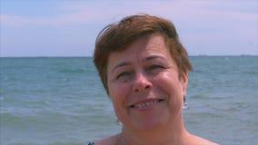 Ώριμη όμορφη ευτυχής καυκάσια γυναίκα που εξετάζει τη κάμερα, ευτυχές χαμόγελο γυναικών απόθεμα βίντεο