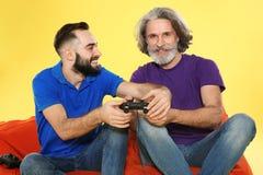 Ώριμοι άτομο και τύπος που παίζουν τα τηλεοπτικά παιχνίδια με τους ελεγκτές στοκ φωτογραφία με δικαίωμα ελεύθερης χρήσης
