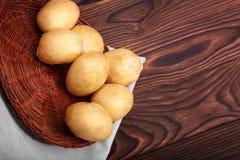 Ώριμοι βολβοί πατατών σε ένα φωτεινό καφετί υπόβαθρο Ένα ξύλινο σύνολο καλαθιών των φρέσκων πατατών σε έναν σάκο Μια τοπ άποψη σχ στοκ εικόνες