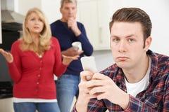 Ώριμοι γονείς που ματαιώνονται με την ενήλικη διαβίωση γιων στο σπίτι στοκ εικόνα
