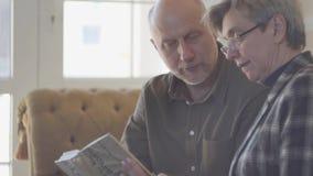 Ώριμοι ζεύγος, άνδρας και γυναίκα, που κάθονται στον καναπέ με ένα βιβλίο και που μιλούν και που χαμογελούν ο ένας στον άλλο r φιλμ μικρού μήκους