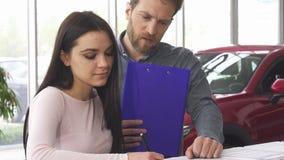 Ώριμος έμπορος αυτοκινήτων που υπογράφει τα έγγραφα με το θηλυκό πελάτη του φιλμ μικρού μήκους