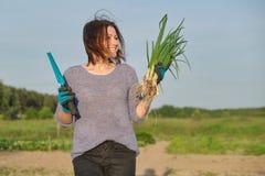 Ώριμος αγρότης γυναικών που περπατά μέσω του κήπου με το πράσινο φρέσκο κρεμμύδι φρέσκων κρεμμυδιών στοκ φωτογραφία