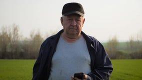 Ώριμος αγρότης που εξετάζει το χώμα και που χρησιμοποιεί το smartphone που ελέγχει την έκθεση της γεωργίας σε έναν τομέα φιλμ μικρού μήκους
