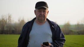 Ώριμος αγρότης που εξετάζει το χώμα και που χρησιμοποιεί το smartphone που ελέγχει την έκθεση της γεωργίας σε έναν τομέα απόθεμα βίντεο