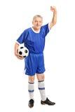 Ώριμος ανεμιστήρας που φορά μια αθλητική ένδυση που κρατά ένα ποδόσφαιρο Στοκ Εικόνες