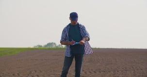 Ώριμος αρσενικός αγρότης που γράφει στην περιοχή αποκομμάτων στο αγρόκτημα Σύγχρονη γεωργία απόθεμα βίντεο