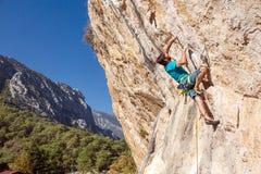 Ώριμος αρσενικός ορειβάτης που αγωνίζεται στο overhanging πορτοκαλή βράχο Στοκ Εικόνα