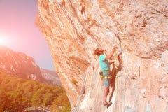 Ώριμος αρσενικός ορειβάτης που κάνει την κίνηση στον κάθετο βράχο Στοκ Εικόνες